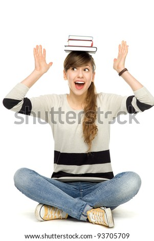 Female student balancing books on head - stock photo
