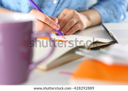 Female student, blogger or designer at workplace holding pencil and writing or making sketches. Woman writing letter, list, plan, making notes, doing homework. Education or creative work concept - stock photo