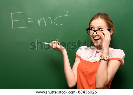 Female student by chalkboard with e=mc2 - stock photo