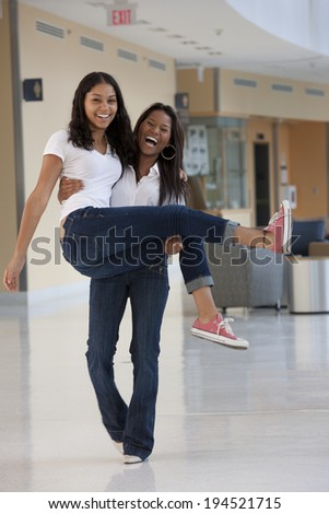 Female student carrying her friend and laughing - stock photo