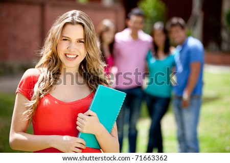 Female student carrying notebooks outdoors and smiling - stock photo