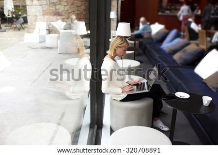 Female student connecting to wireless via laptop computer while sitting in modern coffee shop or university library, modern business woman keyboarding on net-book while working in loft studio interior - stock photo