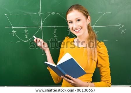 Female Student Doing Math on Chalkboard - stock photo