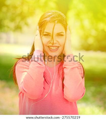 Female student girl outside in park listening to music on headphones - stock photo
