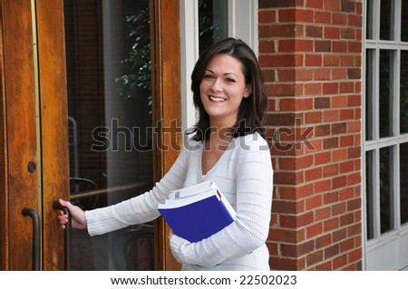 Female student going to class with books in hand. - stock photo