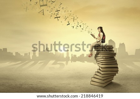 Female student holding book while sitting on books and think about her dream in 2015 - stock photo