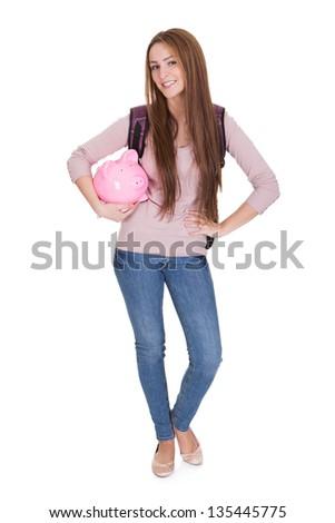 Female Student Holding Piggybank Over White Background - stock photo