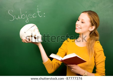 Female student holding skull and book - stock photo