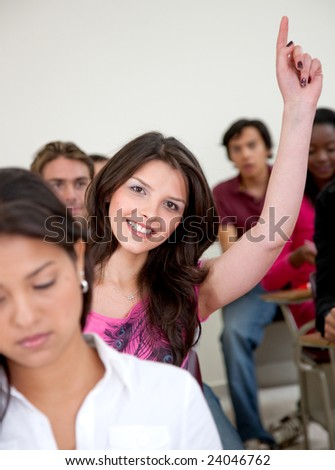 Female student in a classroom - participating and smiling - stock photo