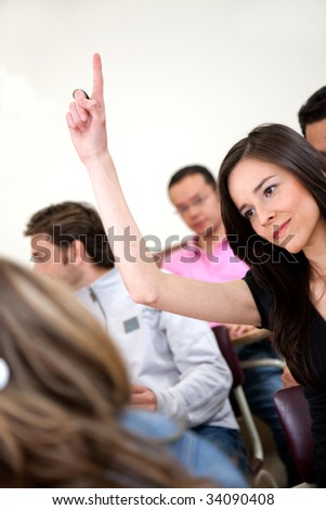 Female student in a classroom, participating and smiling - stock photo