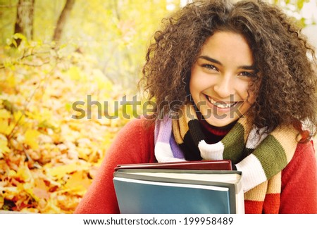 Female student in warm autumn. A smiling cute young female student with books in hand on the background of the autumn landscape - stock photo