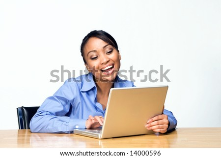 Female student laughs while looking at laptop. Horizontally framed photograph - stock photo