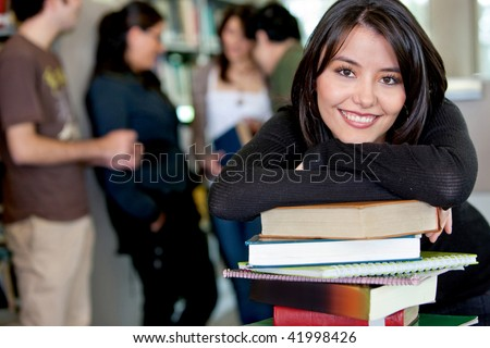 Female student leaning on books at the library with her friends behind - stock photo