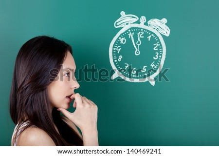 female student looking at a drawn clock showing five to twelve - stock photo