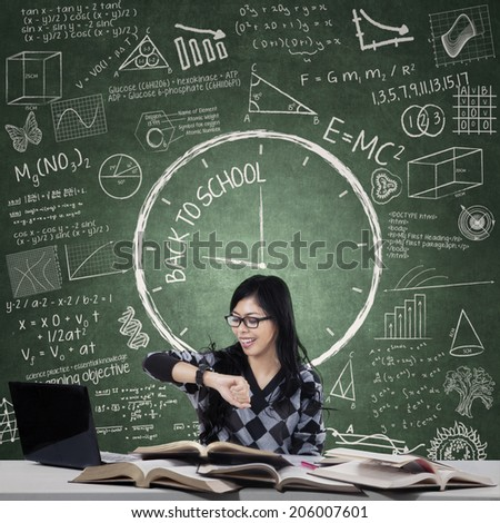 Female student looking at wristwatch while studying - stock photo