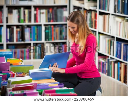 Female student looking for a library book - stock photo