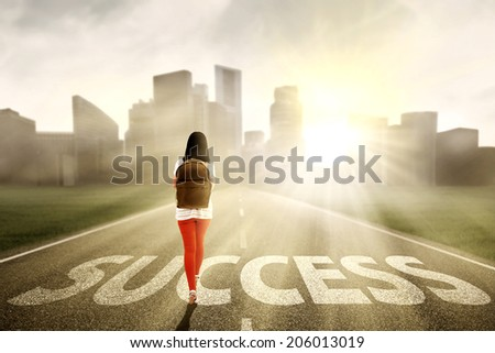 Female student looking for success and walking on the highway of a skyscraper with cityscape - stock photo