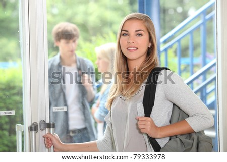 Female student opening door - stock photo