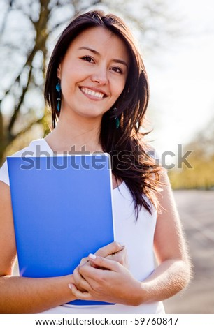 Female student outdoors holding a notebook and smiling - stock photo
