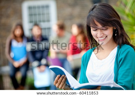Female student outdoors with a group of people on the background - stock photo