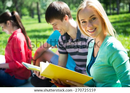 Female student outdoors with her friends - stock photo