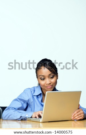 Female student partially smiling while looking at laptop. Vertically framed photograph - stock photo
