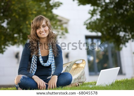 Female Student Portrait sitting outside an academic building - stock photo