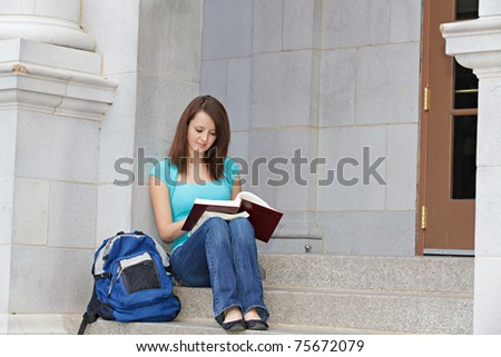 Female student reading at school outside - stock photo