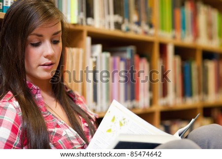 Female student reading in a library - stock photo