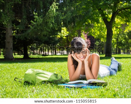 Female student reading outdoor in park. Happy caucasian college student lying down on grass on summer. Copy space. - stock photo