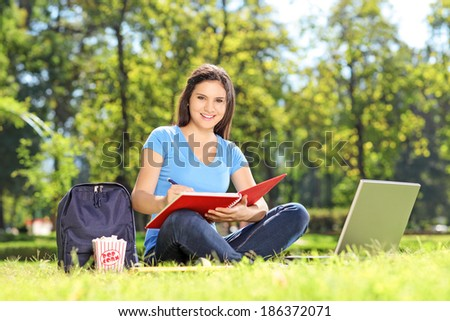 Female student relaxing outdoors - stock photo
