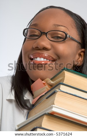Female Student rests her head on stack of books - stock photo