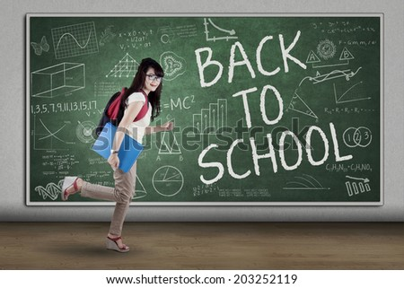 Female student running to school. shot in the class - stock photo