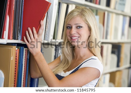 Female student selecting book from library shelf - stock photo