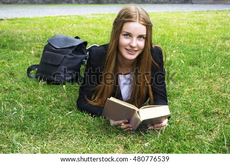Female student sits on the grass with textbook, European, White,Caucasian