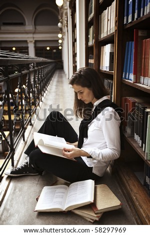 Female student sitting at bookshelf in old library reading books. - stock photo