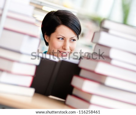 Female student sitting at the desk is surrounded with piles of books. Educational process - stock photo