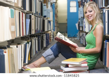 Female student sitting on library floor surrounded by books - stock photo