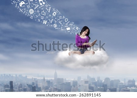 Female student sitting on the cloud while using a digital tablet to share information - stock photo