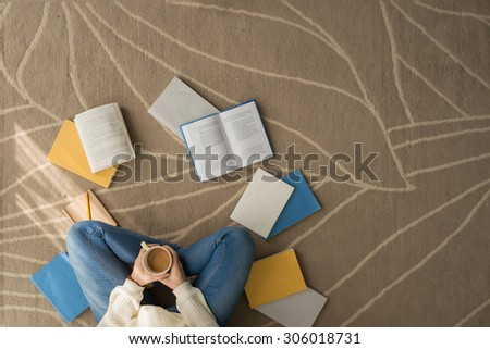 Female student sitting on the floor with a cup of cacao and reading textbooks - stock photo