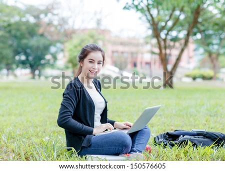 female student sitting on the green field with laptop computer
