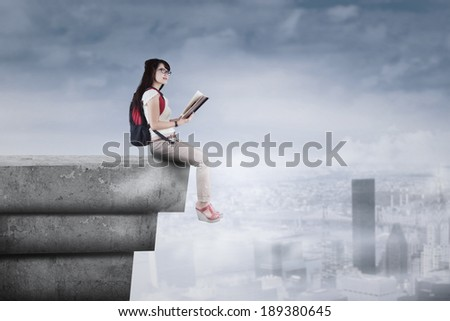 Female student sitting on the rooftop while holding a book - stock photo