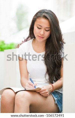 Female student sitting outdoors and writing something in notebook