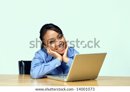 Female student smiles at the camera as she holds her face in her hands. Horizontally framed photograph - stock photo