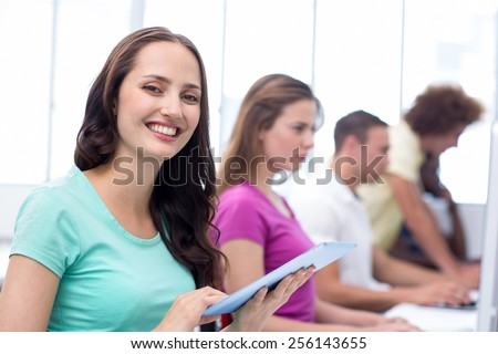 Female student smiling at camera in computer class