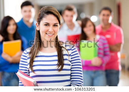 Female student smiling with a group of people at the background - stock photo