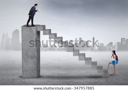 Female student stepping up on the stair for meeting with her teacher on the top
