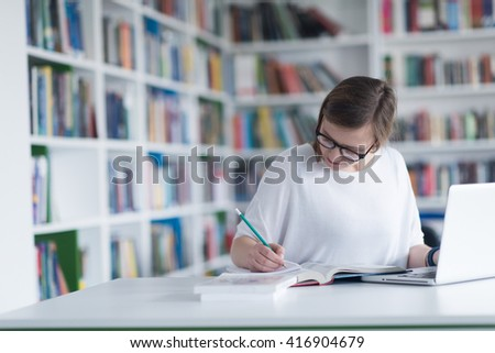 female student study in school library, using laptop and searching for information on internet