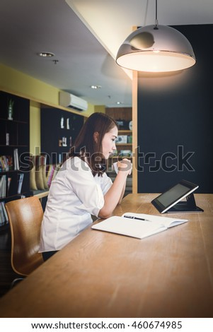 female student study in school library, using tablet, laptop and searching for information on internet