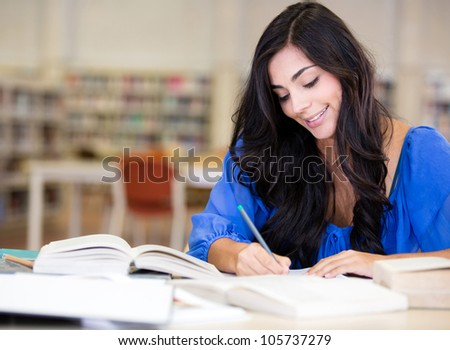 Female student studying at the library and smiling - stock photo